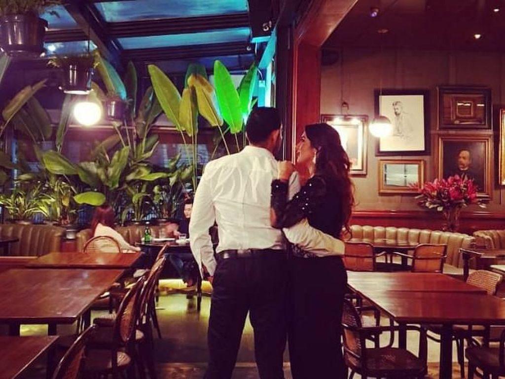 Berpose dari belakang, Abdull dan Tania terlihat mesra dengan saling merangkul di sebuah kafe. Kelihatannya mereka berdua tengah bersiap untuk malam malam. Foto: Instagram @tanianadiraa
