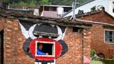 Wu Tsun-hsien berpose di sebuah rumah kosong di desanya yang dindingnya sudah digambari. (AFP PHOTO/Sam Yeh)