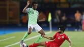 Gelandang Nigeria Alex Iwobi diadang pemain Tunisia Ferjani Sassi. Iwobi merupakan andalan di klub Liga Inggris Arsenal. (REUTERS/Mohamed Abd El Ghany)