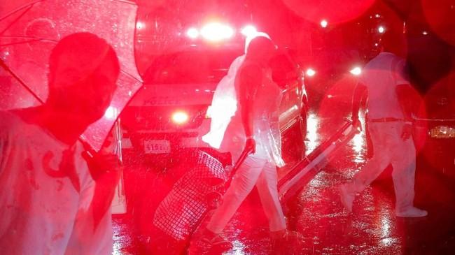 Para pengunjung acara makan malam NYC Diner en Blanc di New York, AS, meninggalkan lokasi di tengah guyuran hujan lebat. (REUTERS/Andrew Kelly)