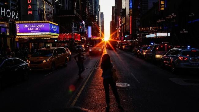 Orang-orang mengambil gambar matahari yang terbenam di kota Manhattan di Times Square, New York City. Area yang populer sebagai Manhattanhenge ini terkenal karena trayeksi mataharinya sejajar dengan bangunan dan jalanan. (REUTERS/Eduardo Munoz)