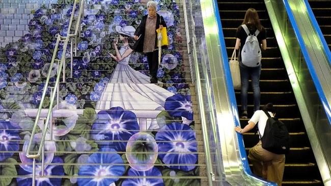 Di pintu masuk stasiun JR Kumagaya di Kumagaya, Prefektur Saitama Jepang, seorang penumpang kereta menuruni tangga yang dihiasi oleh gambar seorang gadis yang dikelilingi bunga. (Photo by Kazuhiro NOGI / AFP)