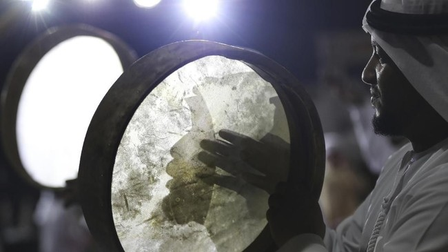 Bayangan seorang seniman terpantul di gendang tradisional yang ia mainkan pada hari pembuka festival Liwa Dates di Liwa, sekitar 350 kilometer dari Dubai, Uni Emirat Arab. (AP Photo/Kamran Jebreili)