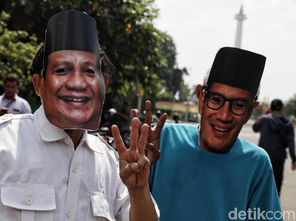 Dua orang warga yang memakai topeng berpose tiga jari. Menurut mereka kini sudah tidak ada lagi 01 dan 02. Yang ada adalah 03 yakni persatuan Indonesia.
