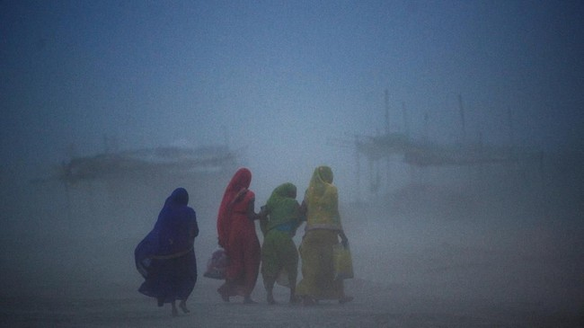 Para perempuan India berjalan melewati badai debu di Sangam, atau delta Sungai Gangga, Yamuna dan Saraswati di Allahabad. (Photo by SANJAY KANOJIA / AFP)