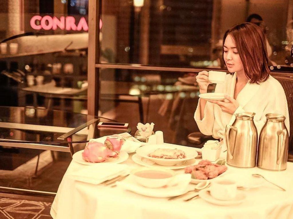 Liburan di Singapura, Wika terlihat santai menikmati aneka makanan dan minuman. Tampaknya ini pemandangan di kamar hotel dan Wika menikmati menu sarapannya. Foto: instagram @wikasalim