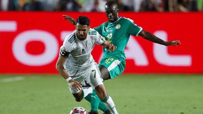 Kapten Aljazair Riyad Mahrez coba menguasai bola dan menjauh dari kejaran Youssouf Sabaly. (REUTERS/Amr Abdallah Dalsh)