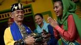 Seorang perwakilan Abang None menyambut pengunjung dengan mengenakan pakaian adat Betawi saat Lebaran Betawi 2019 di lapangan silang Monumen Nasional. (ANTARA FOTO/M Risyal Hidayat)