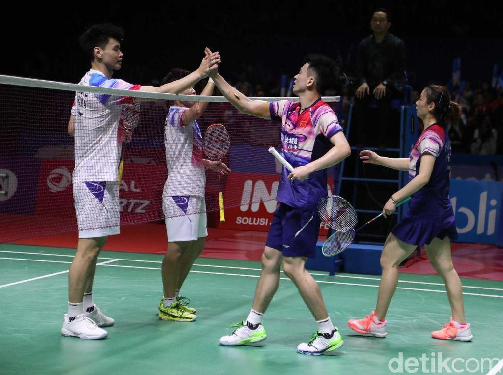 Zheng/Huang dan Wang/Ping saling bersalaman.