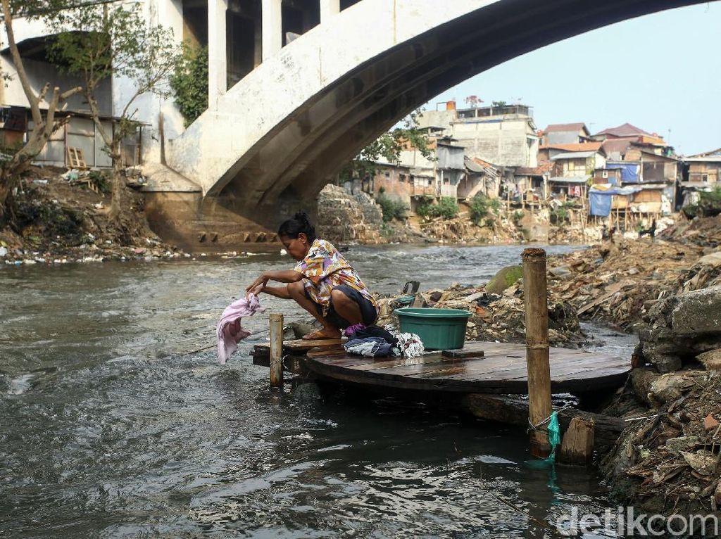 Seorang warga nampak mencuci baju di pinggiran Sungai Ciliwung yang mulai surut.