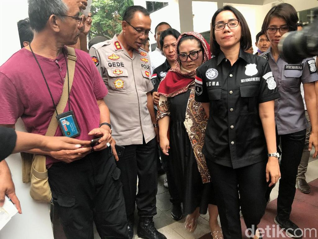 Tak lama kemudian Nunung muncul dengan memakai baju hitam dan hijab tanpa mengenakan masker serta baju tahanan.