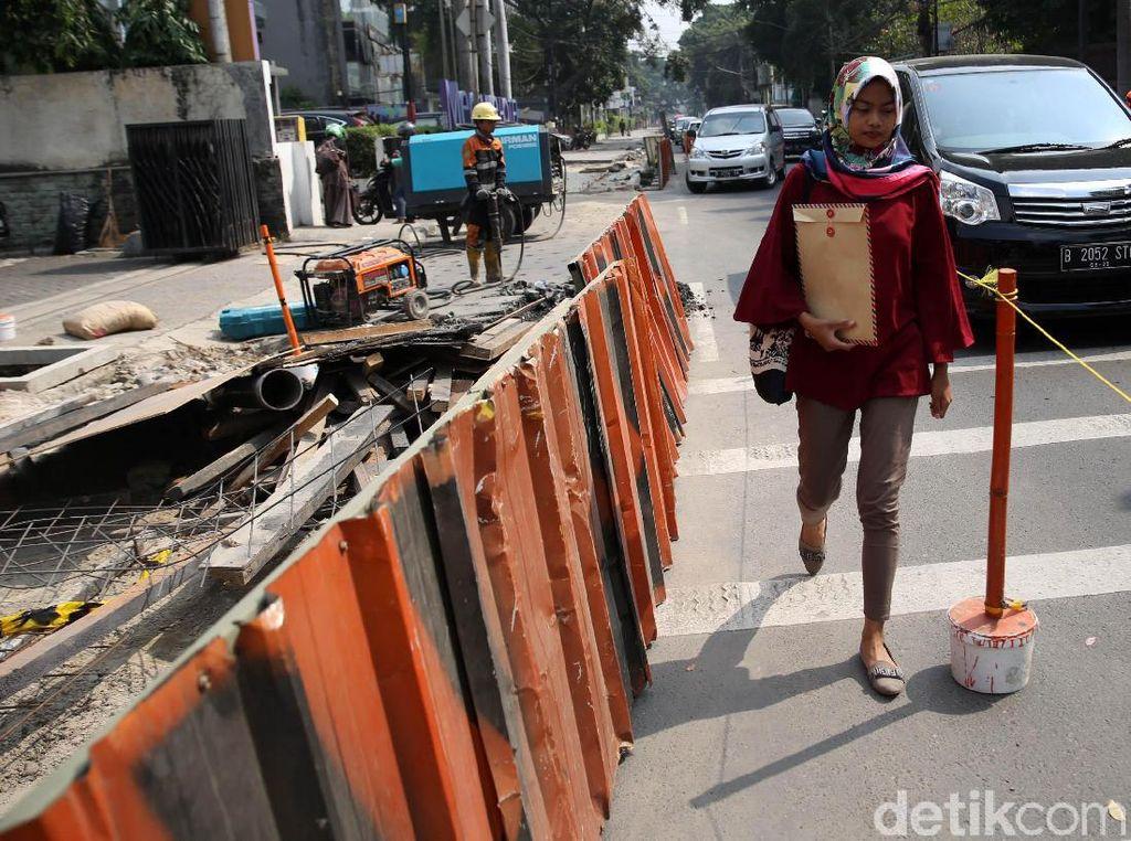 Pejalan kaki harus melewati jalan raya selama proyek pelebaran trotoar berlangsung.