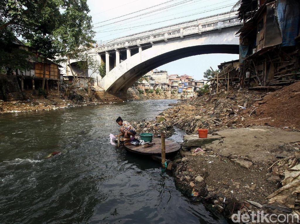 Selain bermain, ada pula warga yang memanfaatkan air Sungai Ciliwung yang mulai surut untuk mencuci pakaian.