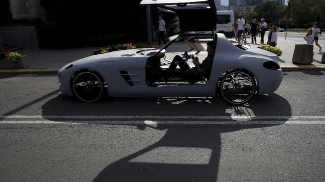 Andrzej Burek terlihat sangat menikmati mengayuh sepeda berbodi mobil sport Mercedes SLS AMG. (REUTERS/Kacper Pempel)