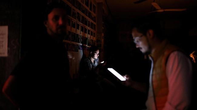 Beberapa warga bermain ponsel di sebuah bar selama pemadaman listrik di Caracas, Venezuela 22 Juli 2019. (REUTERS/Manaure Quintero)