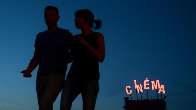 Pasangan-pasangan kerap terlihat waktu intim berdua sembari menonton film, duduk santai di atas rumput. (PHILIPPE LOPEZ / AFP)