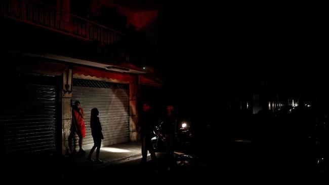 Orang-orang menggunakan lampu sepeda motor sebagai penerangan selama pemadaman di Caracas, Venezuela 22 Juli 2019. (REUTERS/Carlos Garcia Rawlins)