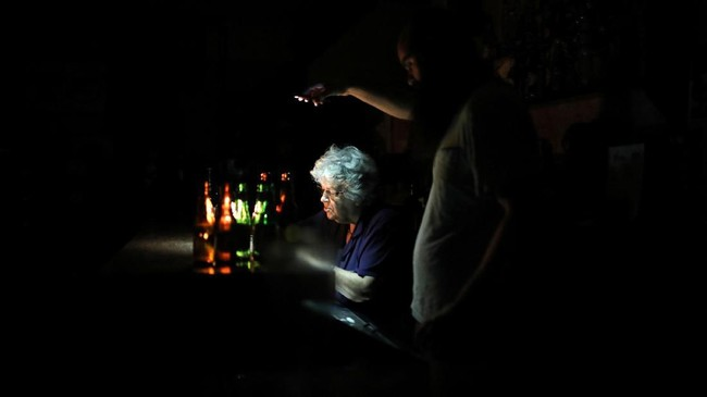 Seorang pria menggunakan ponsel untuk menerangi vendor di sebuah bar saat pemadaman listrik di Caracas, Venezuela, 22 Juli 2019. (REUTERS/Manaure Quintero)