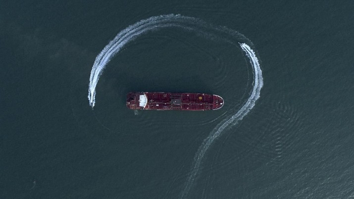 In this Sunday, July 21, 2019 photo, an aerial view shows a speedboat of Iran's Revolutionary Guard moving around the British-flagged oil tanker Stena Impero which was seized in the Strait of Hormuz on Friday by the Guard, in the Iranian port of Bandar Abbas. Global stock markets were subdued Monday while the price of oil climbed as tensions in the Persian Gulf escalated after Iran's seizure of a British oil tanker on Friday. (Morteza Akhoondi/Tasnim News Agency via AP)