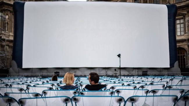 Layar yang disediakan tak hanya satu, tetapi delapan. Tersebar di beberapa tempat, ada juga yang telah disediakan kursi lipat. (Martin BUREAU / AFP)