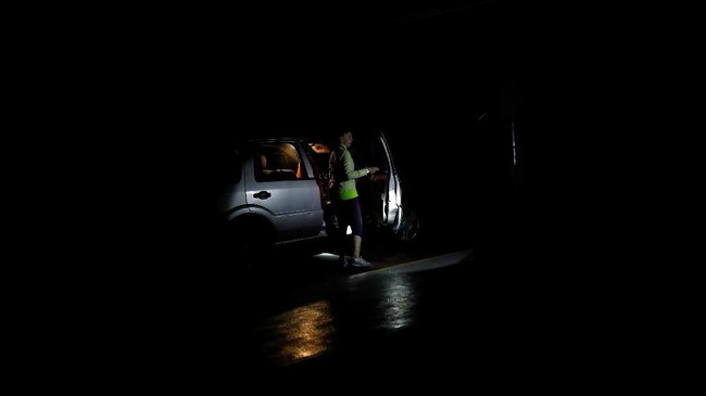 Seorang pria menggunakan senter untuk menerangi wanita yang hendak menaiki mobil ketika terjadi pemadaman di Caracas, Venezuela 22 Juli 2019. (REUTERS/Carlos Garcia Rawlins)