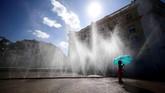 Di Vienna, Austria, seorang gadis berpayung biru berdiri di bawah air mancur pada hari yang diterpa gelombang panas. (Reuters/Lisi Niesner)