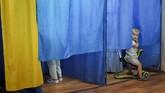 Dari dalam bilik seorang bocah melihat tempat pencoblosan di pemilihan umum anggota parlemen Ukraina di Kiev. (AP/Evgeniy Maloletka)