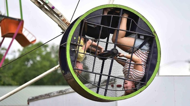 Gianna Haskins (kiri), usia 12, dan kawannya, Alyssa Primel (16) menikmati alat Super Spinner di ajang tahunan Perayaan Asosiasi Relawan Ferndale di Johnstown, Philladelphia. (John Rucosky/The Tribune-Democrat via AP)