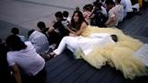 Pasangan kekasih beristirahat di anak tangga di sela-sela sesi pemotretat pernikahan mereka di Bund, Shanghai, China. (Reuters/Aly Song)