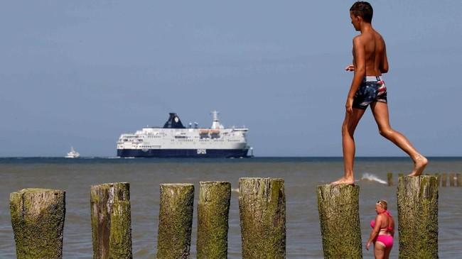 Orang-orang mendinginkan tubuh pada suatu hari yang panas, sementara kapal feri melintasi pantai Sangatte, Perancis. (Reuters/Pascal Rossignol)