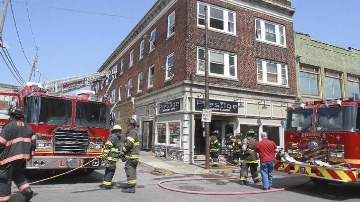 Petugas pemadam kebakaran kota menyelamatkan penduduk dari lantai tiga gedung.