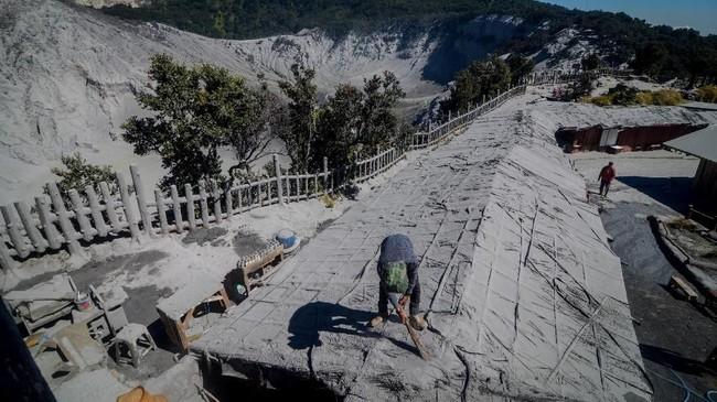 Pedagang membersihkan atap kiosnya dari debu vulkanik pascaerupsi Gunung Tangkuban Parahu, di Kabupaten Subang, Jawa Barat, Senin (29/7). (ANTARA FOTO/Raisan Al Farisi/ama)