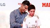 Ronaldo memberi tanda tangan kepada suporter cilik Madrid, Jorge, yang juga sempat bertanya kepada mantan pemilik nomor tujuh di Los Blancos. (REUTERS/Juan Medina)