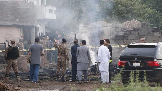 Asap mengepul di udara. Puing pesawat berserakan di sekitar rumah yang juga hancur akibat hantaman burung besi itu. (Reuters/Stringer)