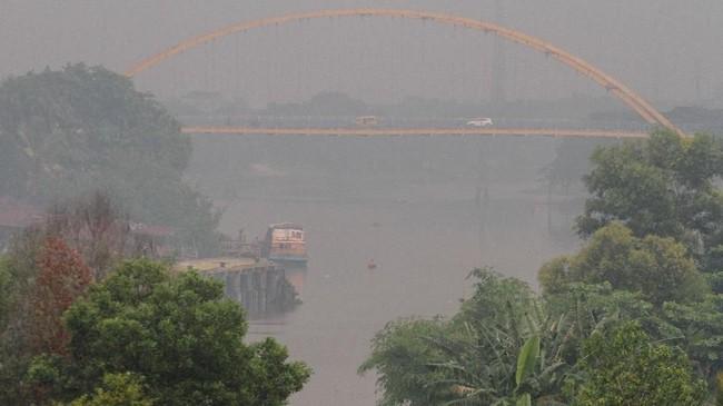Kabut asap dampak dari kebakaran hutan dan lahan yang terjadi di beberapa wilayah di Provinsi Riau terlihat di kawasan Sungai Siak, Pekanbaru, Riau, 30Juli 2019. (ANTARA FOTO/Rony Muharrman)