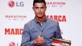 Ronaldo mengangkat trofi Marca Legend yang dianugerahkan kepadanya lantaran kesuksesan di bidang olahraga sepak bola. (REUTERS/Juan Medina)