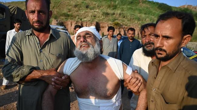 Lara menyelimuti warga Pakistan ketika sebuah pesawat militer jatuh di perumahan mereka di Kota Rawalpindi pada Selasa (30/7) dan merenggut 17 nyawa. (AFP Photo/Aamir Qureshi)