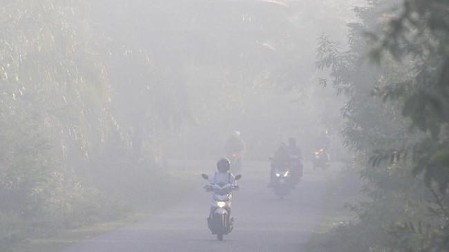 Sejumlah pengguna jalan menembus kabut asap yang menutupi kawasan jalan Desa Suak Timah, Samatiga, Aceh Barat, Aceh, 30Juli 2019. (ANTARA FOTO/Syifa Yulinnas)