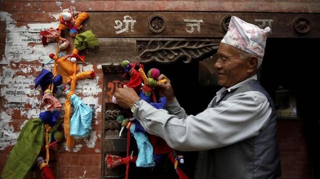 Ghantakarna digambarkan memiliki tubuh yang dicat warna merah, biru, dan hitam. Ia juga mengenakan sepasang lonceng di telinga. (REUTERS/Navesh Chitrakar)