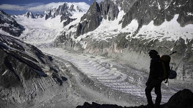 Seorang pria berdiri di atas gletser Mer de Glace di Chamonix, Rabu (19/6). (AFP/Marco Bertorello).