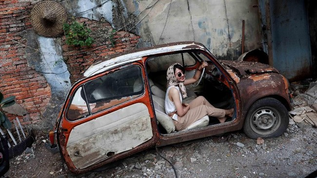 Seorang perempuan berpose di dalam mobil yang diparkir di jalanan sebagai daya tarik wisata Bangkok, Thailand pada Minggu (29/7). (Reuters/Soe Zeya Tun).