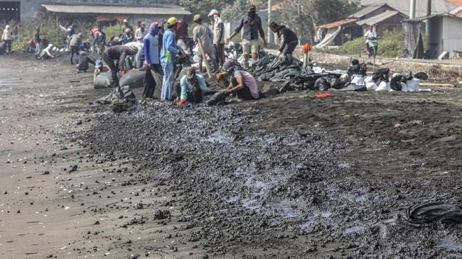 Warga mengumpulkan limbah tumpahan minyak