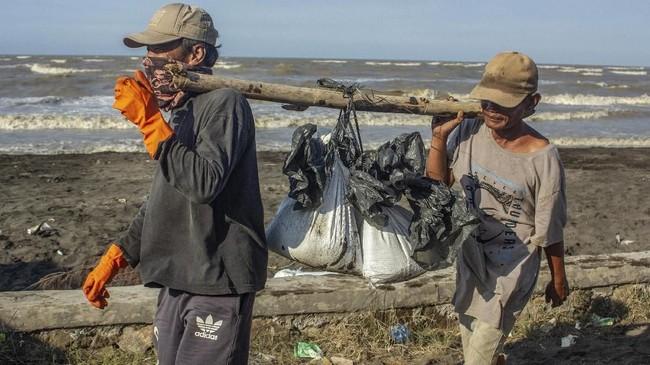 Warga membawa karung berisi pasir yang tercemar tumpahan minyak mentah (Oil Spill) di pesisir Pantai Cemarajaya, Karawang, Jawa Barat. PT Pertamina disebut akan memberi kompensasi kepada nelayan yang terkena dampak kebocoran minyak di Blok ONWJ. (ANTARA FOTO/M Ibnu Chazar)