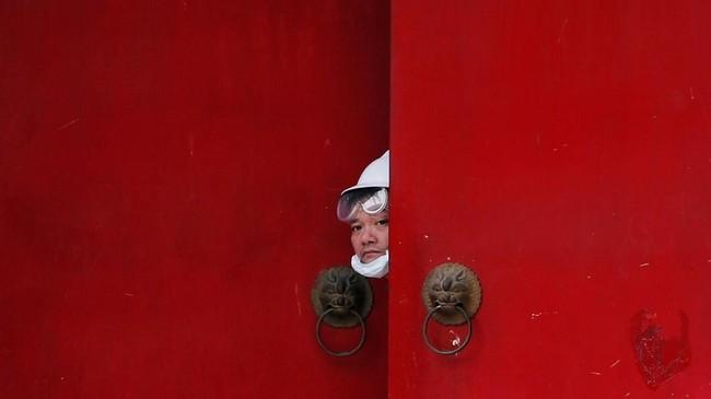 Seorang pria berbaju putih mengintip dari pintu masuk Desa Nam Pin Wai saat protes dilakukan terhadap aksi Yuen Long di Yuen Long, Hong Kong, Sabtu (27/7). (Reuters/Tyrone Siu).