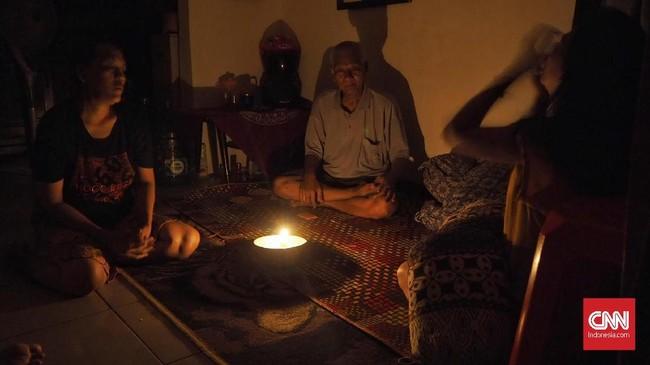 Warga bercengkerama di dalam rumah ketika listrik masih padam di Karet Tengsin, Jakarta, Minggu (4/8). PLN menepis isu sabotase dalam insiden kerusakan sejumlah jaringan listrik. (CNN Indonesia/Safir Makki)