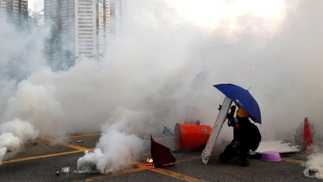 Sementara itu, di ruas-ruas jalan protokol Hong Kong, para demonstran melakukan berbagai upaya blokade hingga menyebabkan kemacetan total. Aparat pun menembakkan gas air mata untuk membubarkan massa. (REUTERS/Tyrone Siu)