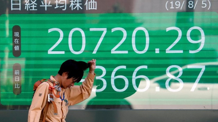 A man paues in front of an electric screen showing Japan's Nikkei share average outside a brokerage in Tokyo, Japan, August 5, 2019.   REUTERS/Issei Kato