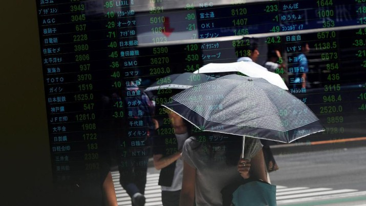 Passersby are reflected on an electronic board showing the exchange rates between the Japanese yen and the U.S. dollar, the yen against the euro, the yen against the Australian dollar, Dow Jones Industrial Average and other market indices outside a brokerage in Tokyo, Japan, August 6, 2019.   REUTERS/Issei Kato