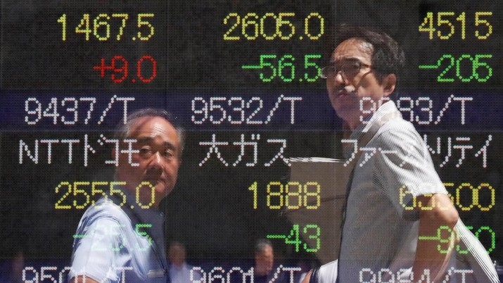 Passersby are reflected on a stock quotation board outside a brokerage in Tokyo, Japan, August 6, 2019.   REUTERS/Issei Kato
