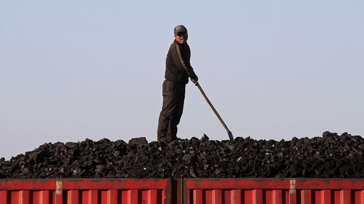 FILE PHOTO: A worker speaks as he loads coal on a truck at a depot near a coal mine from the state-owned Longmay Group on the outskirts of Jixi, in Heilongjiang province, China, October 24, 2015. REUTERS/Jason Lee/File Photo